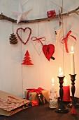 Weihnachtsdeko an rustikalem Ast hängend, darunter Kerzenhalter mit brennenden Kerzen