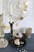 Gold bemalte Steine in schwarzer Backform und Kerzenhalter mit weissen Kerzen weihnachtlich geschmückt, vor Girlande aus goldenen Papierplättchen