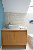 Washstand with pale wooden base unit under sloping ceiling