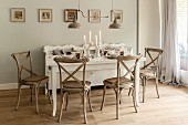 White, set dining table, wooden chairs and lit candles in vintage-style dining room