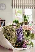 In Papier eingewickelter Blumenstrauss auf Tisch