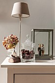 Glass jar full of conkers, table lamp, vase of hydrangeas and wooden sculptures in glass display case