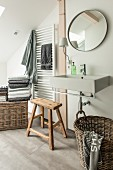 Modern sink below round mirror on wall with rustic wooden stool and wicker basket below