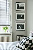 View past scatter cushions on bed to black and white photos on pale grey wall next to window