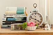 Silver tin and rose in pot in front of stacked books and vintage-style alarm clock
