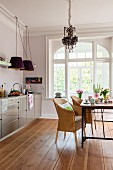 Wicker armchairs and modern, glossy kitchen counter in dining area of period apartment with wooden floor
