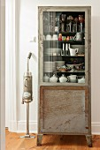 Retro vacuum cleaner next to crockery in vintage glass-fronted cabinet
