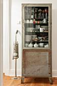 Vintage Vitrinenschrank mit Geschirr, daneben Retro- Staubsauger
