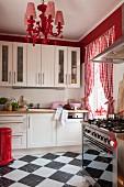 Schachbrettfliesen, rot-weiss karierte Vorhänge und poppiger Kronleuchter in weisser Küche