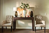 Polstersessel neben Wandtisch mit Tischleuchten und silberfarbener Vase mit weißen Blütenzweigen