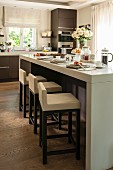 Elegant breakfast bar and upholstered bar stools in open-plan kitchen