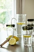 Lemons, glass of water and jug of water on table