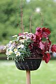 Alte Gugelhupfform mit Margeriten und roten Blättern als Gartendeko