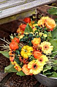 Autumnal bouquet of ornamental squashes, roses, physalis, gerbera daisies and red berries