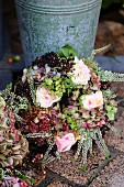 Autumnal wreath of dried hydrangeas, roses, elderberries and heather leaning against zinc bucket