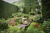 Blick in idyllischen grünen Garten mit hohen Hecken, Steinplattenweg, Wasserlauf und Holzsteg