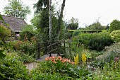Small wooden bridge with handrail leading between flowering perennials and foliage plants in summer garden
