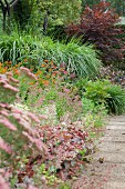 Flowering herbaceous border and stone-flagged garden path