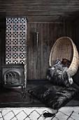 Ein Hängesessel aus Korb in einem dunklen Zimmer mit Bollerofen