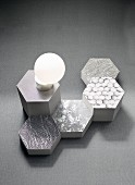 Fabric patterns on honeycomb-shaped objects in shades of grey and an opal glass lamp