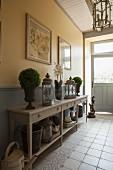 Mit Laternen und Bäumchen dekorierter Konsolentisch in ländlichem Hausflur