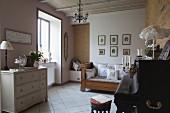 Antike Tagesliege mit nostalgischen Kissen und helle Schubladenkommode in Musikzimmer mit Klavier