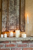 Various lit white candles on rustic mantelpiece below antique wooden panel mounted on wall