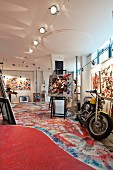 Artist's studio in loft with colourful pictures on wall, brightly painted floor and motorbike at the front right