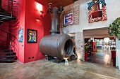 Enormous old industrial stove against bright red wall in loft apartment with stairs leading to gallery