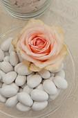 Apricotfarbene Rosenblüte und Hochzeitsmandeln in Glasschale