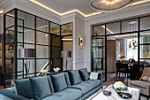 Sofa with blue, sheeny upholstery in front of glass partition with open door and view into dining room