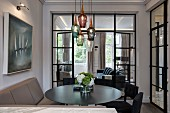 Upholstered bench, black chairs and round table below pendant lamps with glass lampshades of various colours in front of glass partition wall