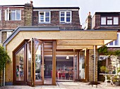 Modern wood and glass extension and terrace behind English terrace house