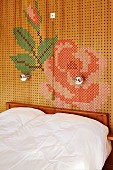 Doppelbett an Wand mit Lochholzpaneelen, darauf Blumenmuster in Stick-Optik