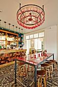 In Barbereich minimalistische Theke und Barhocker auf Fliesenboden mit Vintage Ornament Muster, unter Hängeleuchte aus Metallringen und aufgehängtem Besteck in Pink