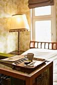Espressotasse auf Tablett, im Hintergrund Stehlampe neben Bett