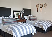 Twin beds with upholstered headboards, striped bed linen and three old tennis racquets on wall