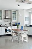Kleiner Essplatz mit Klappstühlen in moderner Einbauküche, blaue Akzente durch Blumenstrauss und Flasche auf dem Tisch