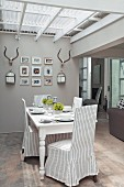 Striped, loose-covered chairs in front of antlers and pictures on wall of dining area