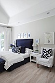 Bright bedroom with elegant dark blue bed, scatter cushions with graphic patterns and gallery of pictures