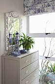 Chinese porcelain on chest of drawers and mirror with floral frame in front of window with toile de jouy Roman blind
