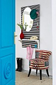 View past bright blue interior door to DIY cloakroom panel with hat pegs, mirror and shelf on black-and-white-striped back