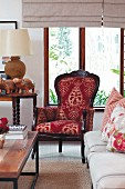 Antique armchair with ornate upholstery, plain sofa with floral scatter cushions and coffee table
