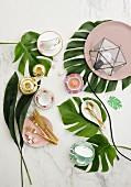 Tischdekoration mit grünen Pflanzenblättern, nostalgischen romantischen Kaffeetassen und Goldbesteck auf marmorierter Tischplatte