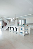 Designer kitchen in open-plan white interior with black 'Bombo' bar stools at elegant island counter