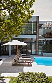 Sun loungers and parasol next to swimming pool in front of modern glass wall