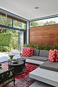 Lounge area with modern grey sofa, red and white scatter cushions and sliding glass wall leading to summery terrace