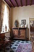 Antike edle Kommode mit Skulpturen und Kerzenständer, seitlich drapierter Vorhang am Fenster