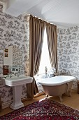 Free-standing bathtub below window with light brown draped curtains next to vintage pedestal sink in traditional ensuite bathroom