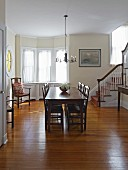 Dark wooden dining table and chairs in traditional dining room with staircase to one side
